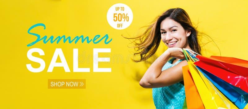 Vente d'été avec la jeune femme heureuse tenant des paniers image libre de droits