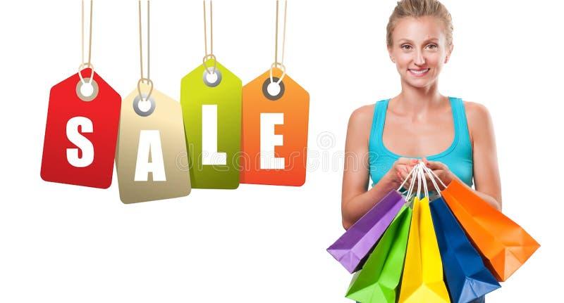 Vente d'achats La femme heureuse tient des paniers image stock