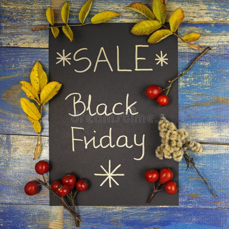 Vente de Black Friday écrite sur la carte noire avec des feuilles et des fruits roses sauvages image stock