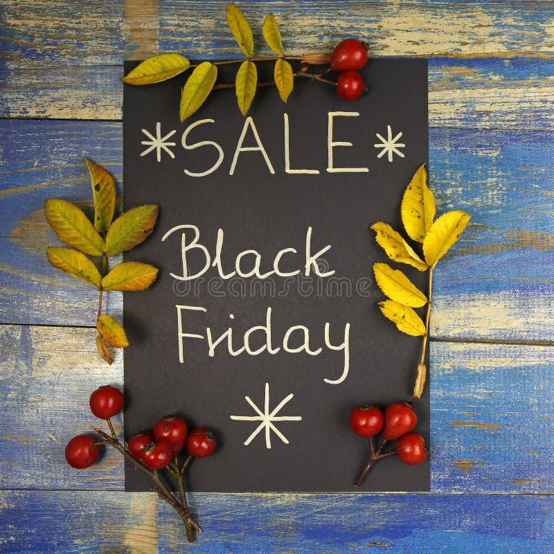 Vente de Black Friday écrite sur la carte noire avec des feuilles et des fruits roses sauvages photos stock