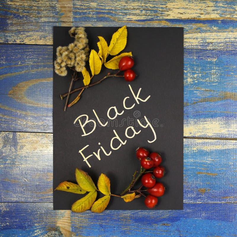 Vente de Black Friday écrite sur la carte noire avec des feuilles et des fruits roses sauvages photographie stock