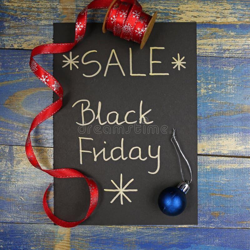 Vente de Black Friday écrite sur la carte noire avec le ruban rouge de Noël photo stock