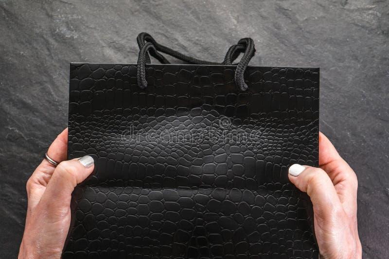 Vente de Black Friday, paquet noir dans des mains femelles photographie stock libre de droits