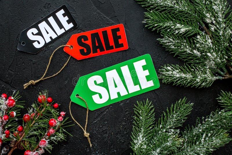 Vente de l'hiver La vente marque près des branches impeccables sur la vue supérieure de fond noir images stock