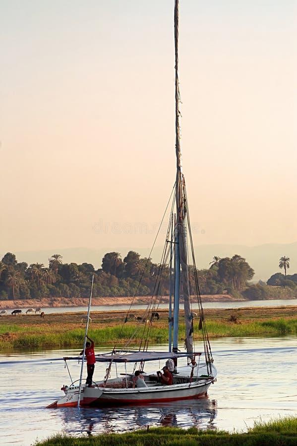 Vente de touristes sur le felucca sur le Nil sur le coucher du soleil en Egypte photographie stock libre de droits
