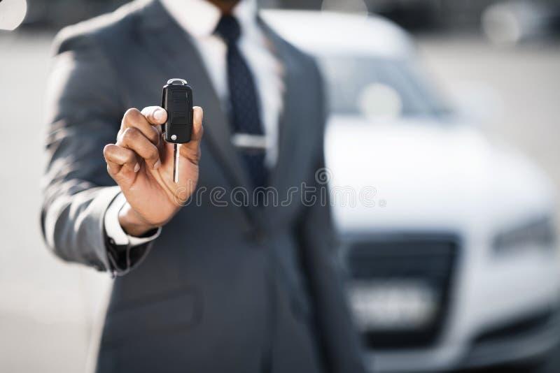 Vente de voiture et concept de location Clé de voiture d'apparence d'homme d'affaires images stock