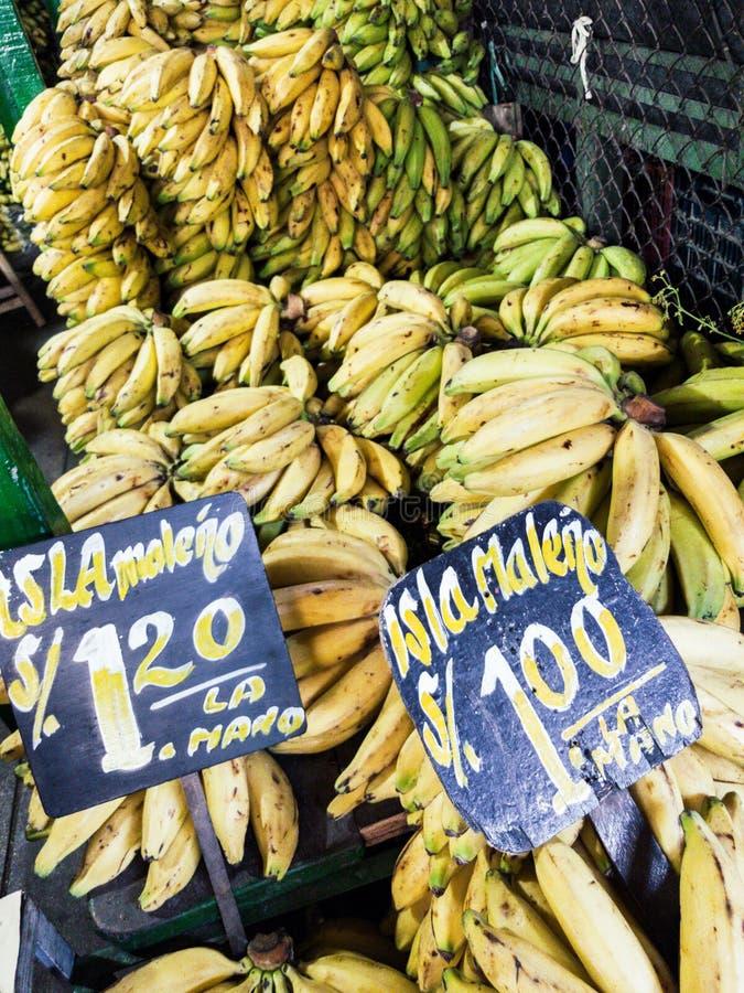 Vente des bananes sur le marché avec les signes qui indiquent le type de banane qui est vendue : image stock