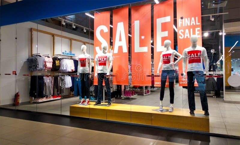 Vente des textes sur l'affiche rouge et les mannequins se tenant dans l'affichage de fenêtre de magasin du magasin des vêtements  photographie stock libre de droits