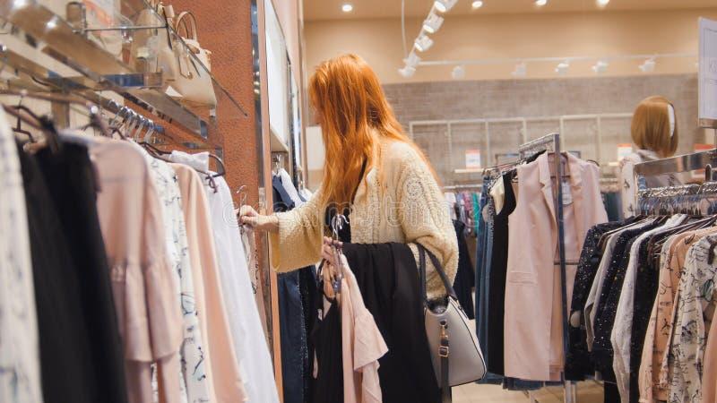 Vente - femme dans le magasin de robe choisit des vêtements - concept d'achats photographie stock libre de droits