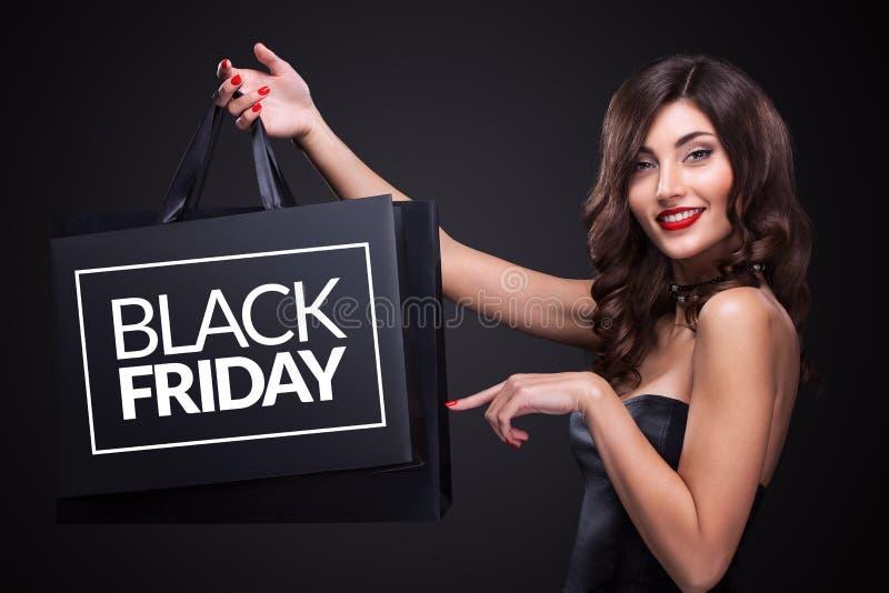 Vente Jeune femme de sourire montrant le panier dans des vacances noires de vendredi photo libre de droits