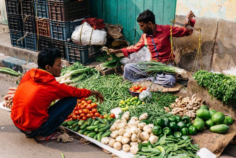 Vente marchande végétale par groupe d'oignon de ressort qui pèsent par les échelles sur le marché de matin dans Kolkata, Inde photos stock