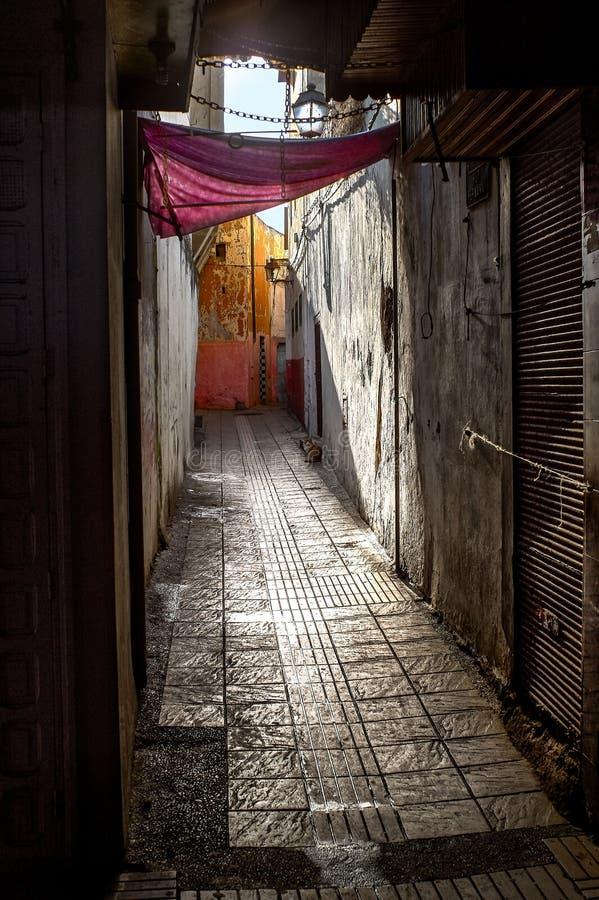 Vente Maroc de contraste La rue étroite de la vieille ville et les vieux, ébréchés murs des maisons sous un auvent rouge pendant  photo stock