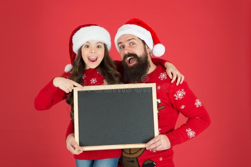 Vente saisonnière Escompte de Noël Concept Happy hours Père Noël Papa et la petite fille qui montre un tableau noir Noël photo libre de droits