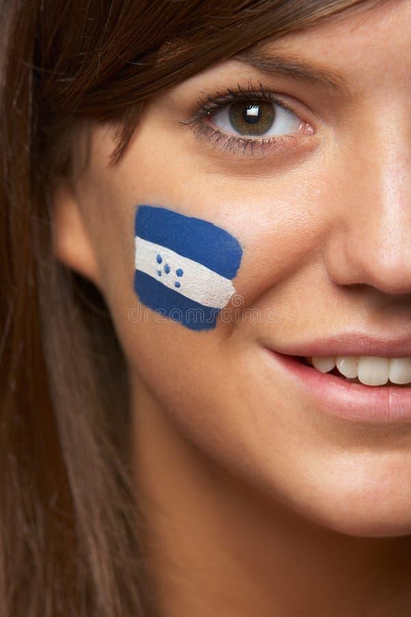 Ventilador de deportes femenino joven con el indicador del Honduran pintado fotografía de archivo libre de regalías