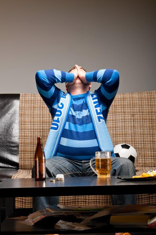 Ventilador de fútbol en el sofá imagenes de archivo
