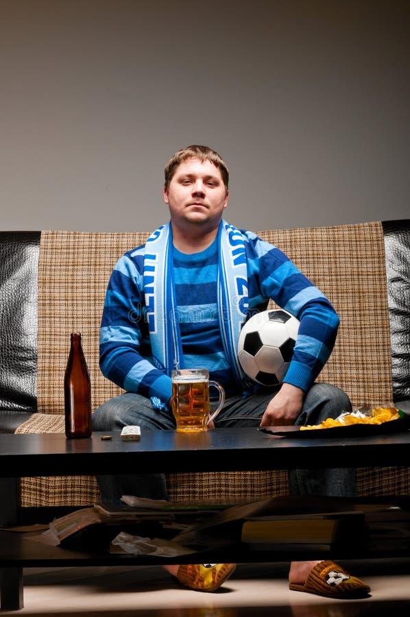 Ventilador de futebol no sofá fotografia de stock royalty free