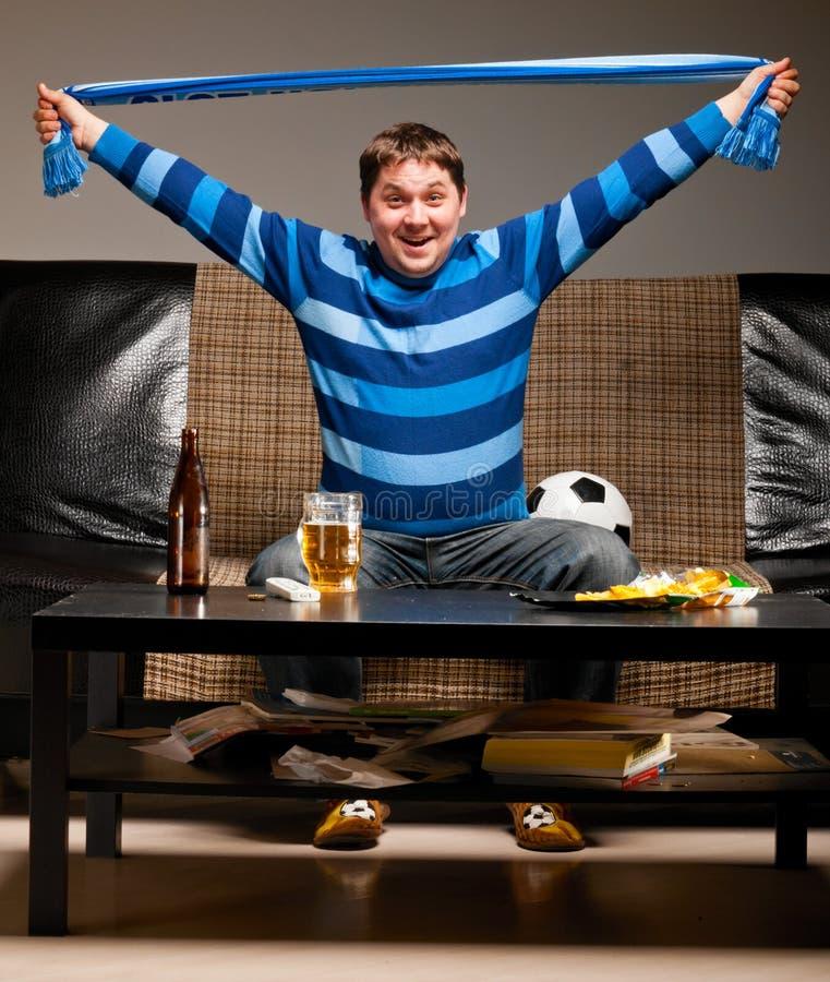 Ventilador de futebol no sofá imagem de stock royalty free