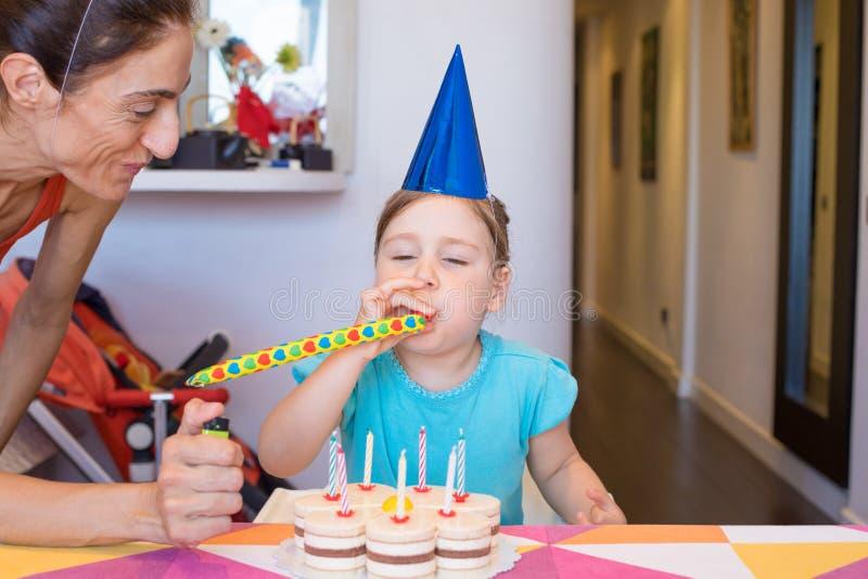 Ventilador de sopro do partido da criança ao lado da mãe e do bolo imagem de stock royalty free