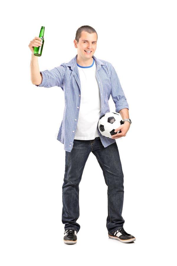 Ventilador masculino eufórico que sostiene un balompié y una cerveza foto de archivo