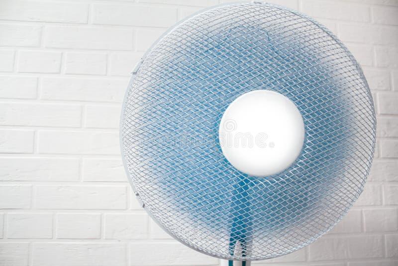 Ventilateur électrique blanc pour l'air frais contre un mur de briques image libre de droits