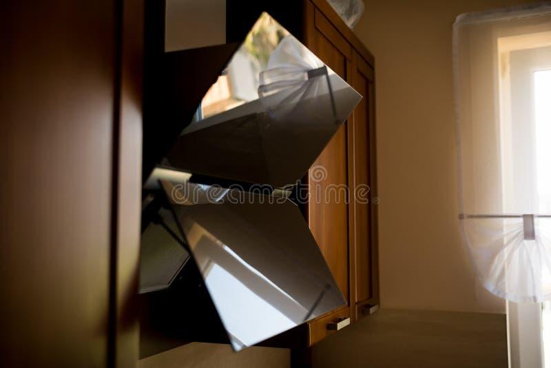 Ventilatiekap van glas in de keuken, met bezinning wordt gemaakt die Mening van kant Houten meubilair op de achtergrond royalty-vrije stock afbeeldingen