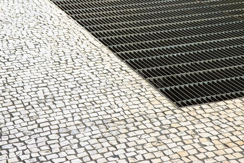 Ventilation iron grid on urban area with stone road - image with copy space.  royalty free stock image