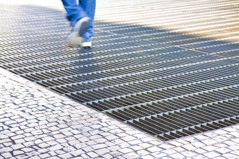 Ventilation iron grid on urban area with stone road - image with copy space.  stock image