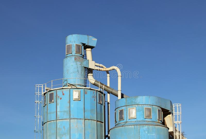 The ventilation system of the wood processing workshop. Metal construction for air circulation in a carpentry factory against a bl stock image