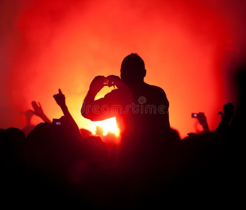 Ventilatorer som tar bilder på konserten arkivbild