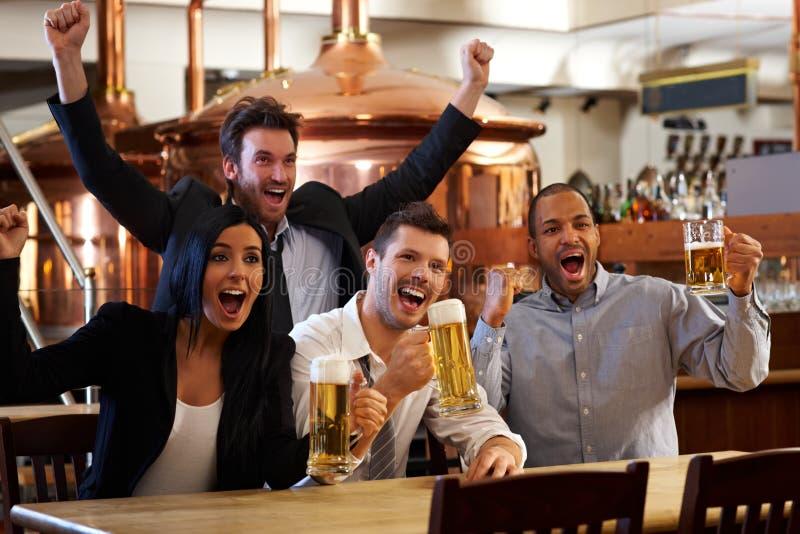 Ventilatori felici che guardano TV nell'incoraggiare del pub immagine stock libera da diritti