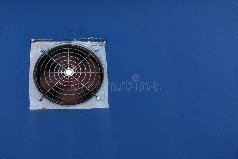 A ventilators built in the blue paint cement wall royalty free stock photo