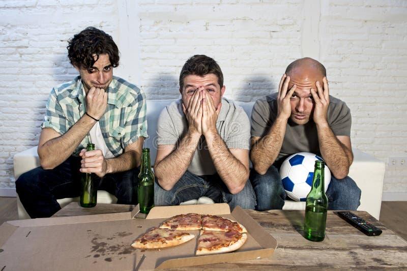 Ventilators die van de vrienden de fanatieke voetbal TV-op gelijke met bierflessen en pizza letten die aan spanning lijden royalty-vrije stock fotografie