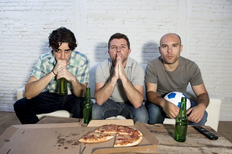 Ventilators die van de vrienden de fanatieke voetbal TV-op gelijke met bierflessen en pizza letten die aan spanning lijden stock afbeelding
