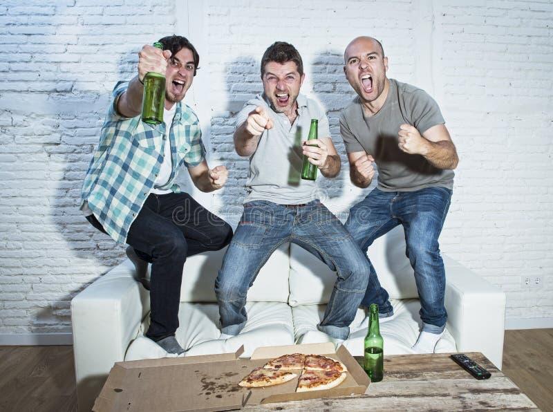 Ventilators die van de vrienden gaan de fanatieke voetbal op spel bij TV-het vieren letten royalty-vrije stock fotografie