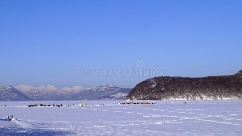Ventiseiesimo gennaio, 2019 - Berry Bay, città di Viljucinsk, penisola di Kamchatka, Russia Gruppo di pescatori su pesca di inver fotografia stock libera da diritti
