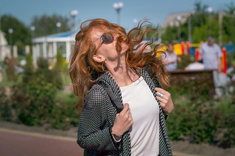 Vento che ondeggia ragazza dai capelli rossi in occhiali da sole fotografia stock