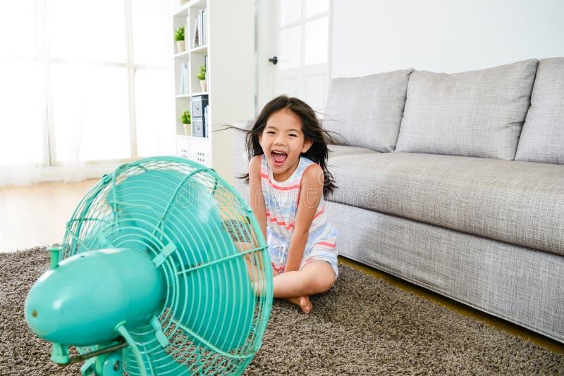 Vento di raffreddamento di salto del bambino femminile attraente felice fotografia stock