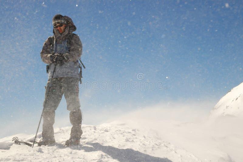 Vento e neve do revestimento do montanhista foto de stock