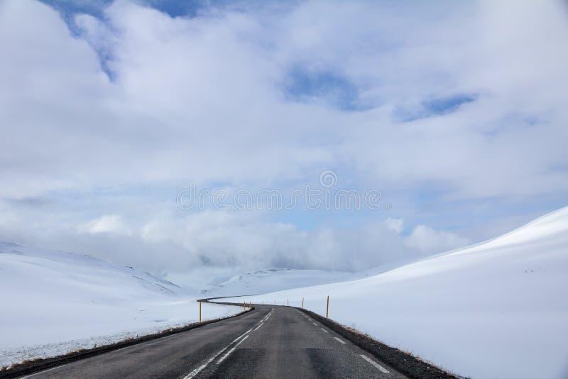 Ventos da estrada do círculo do ` s de Islândia através dos montes cobertos de neve fotos de stock