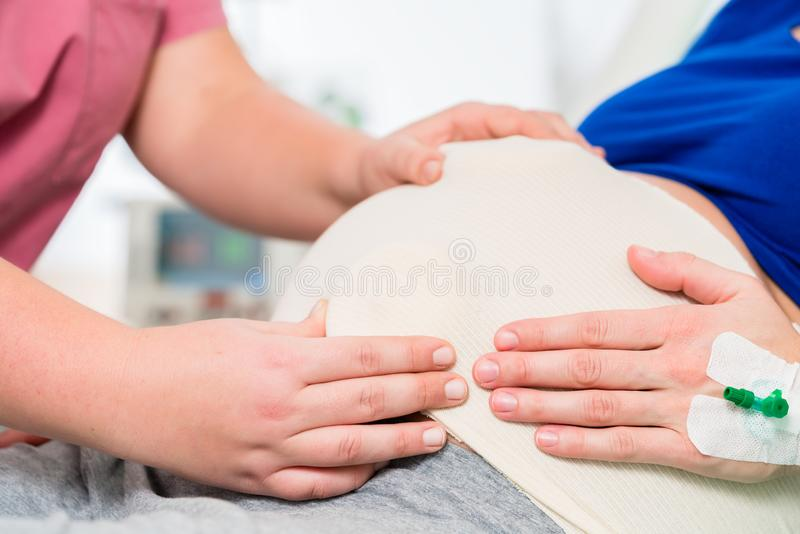 Ventre de bébé de sentiment de sage-femme ou d'infirmière de femme enceinte photographie stock