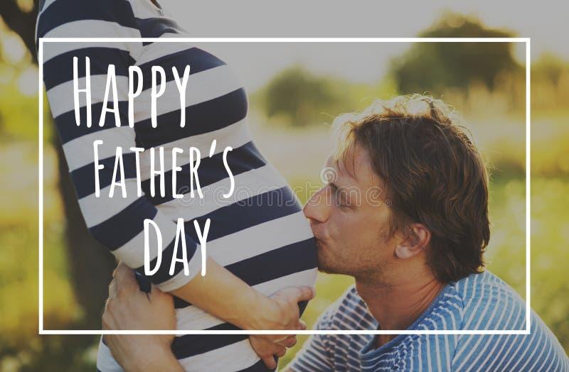 Ventre de baiser de jeune père de son épouse enceinte Jour de pères image stock