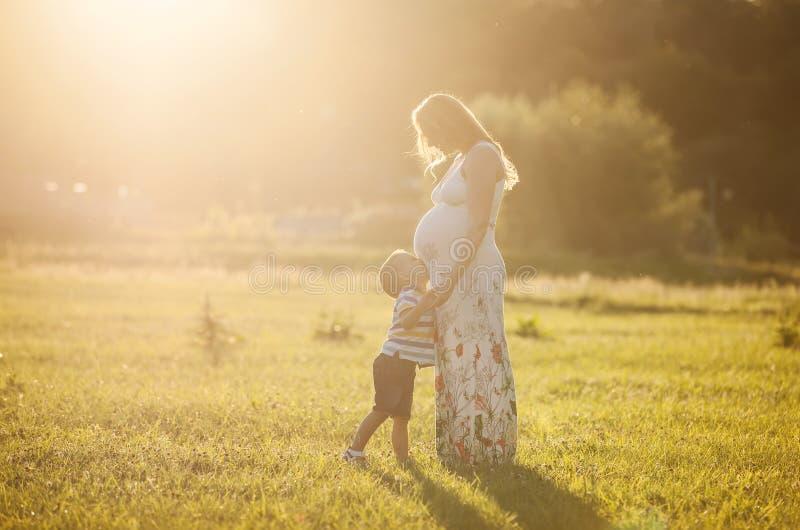 Ventre de baiser de petit garçon de sa mère enceinte photo stock