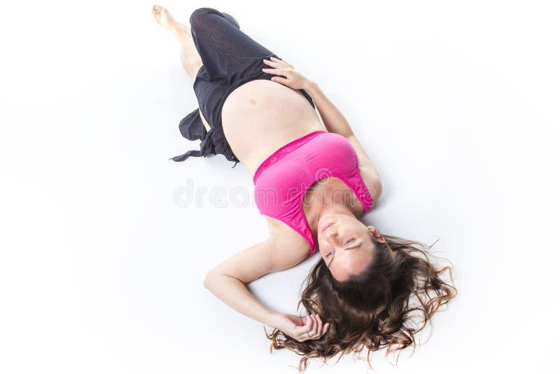 Ventre de femme enceinte au-dessus du fond blanc image libre de droits