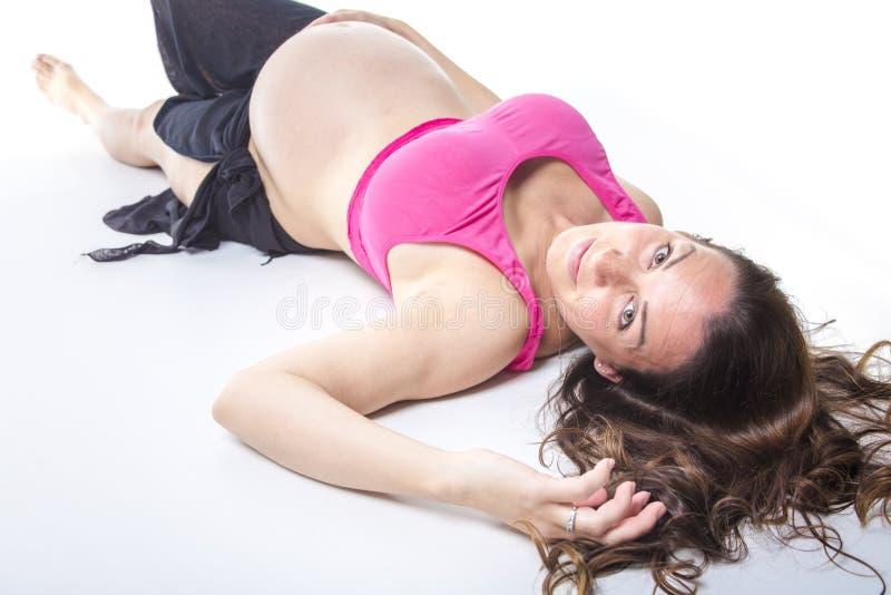 Ventre de femme enceinte au-dessus du fond blanc image stock