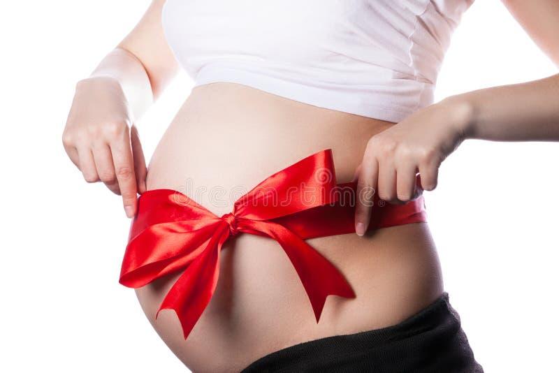 Ventre de femme enceinte avec le ruban rouge et le grand arc image libre de droits