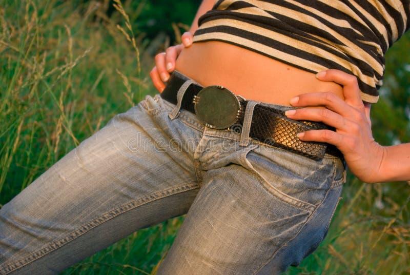Ventre sexy de tan de femme de plan rapproché dans des jeans images libres de droits