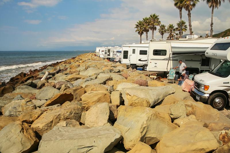 Two men surrounded by several RVs on the rocky beaches of Faria stock photo
