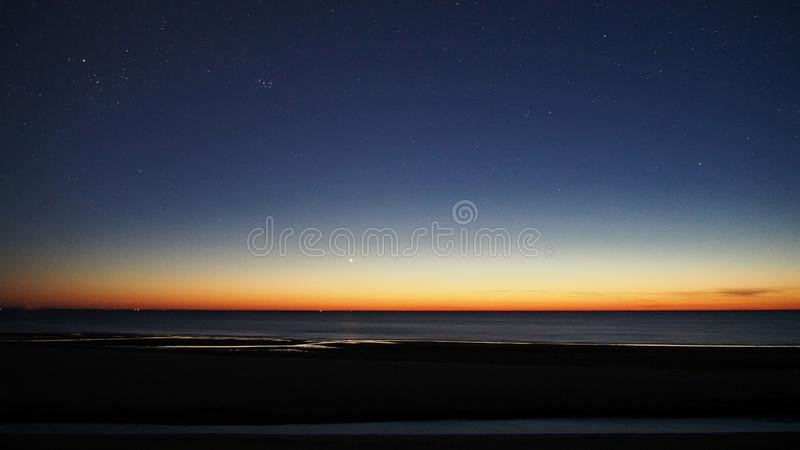 Venus and star cluster Pleiades after sunset. Venus and star cluster Pleiades M45 observing, over sea, after sunset, orange blue sky royalty free stock image