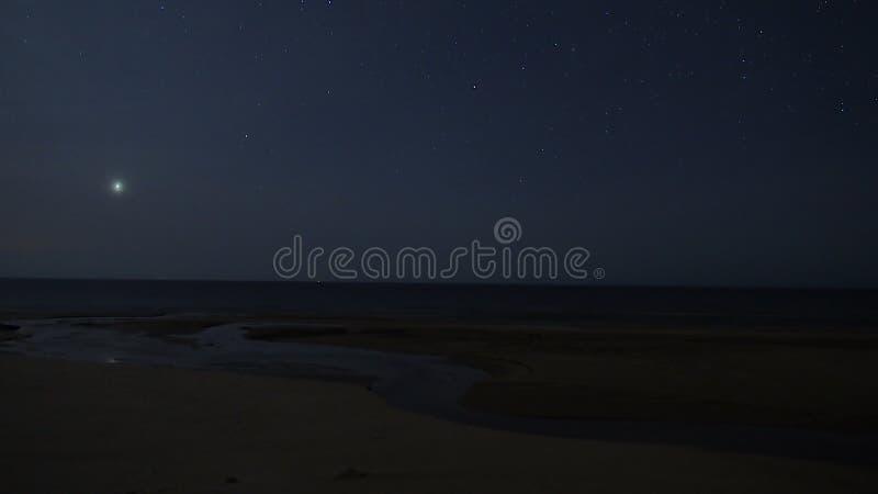 Night sky stars and Venus over sea stock photos