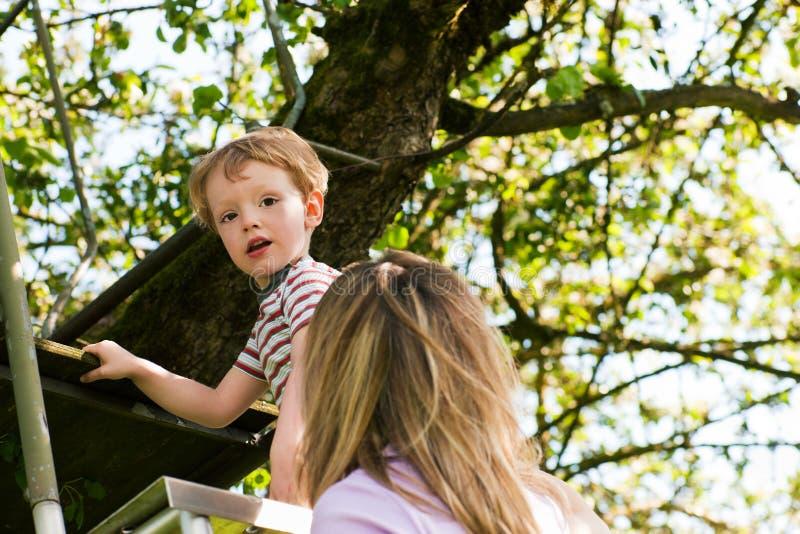 Verão da família na escada à casa de árvore foto de stock royalty free